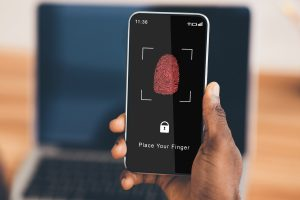 Biometric Authentication Concept. Over The Shoulder View Of Black Guy Holding Smartphone In Hand, Showing App For Fingerprint Scanning With A Zone To Touch With Thumbprint Icon On His Gadget Screen